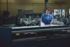 CHISINAU MOLDOVA, KWIECIEŃ, - 26, 2016: Pracownicy w drukowym domu Ludzie pracuje na drukowej maszynie w druk fabryce Przemysłowy Fotografia Stock