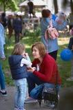 Chisinau, Repubblica di Moldavia - 10 maggio 2019: il gelato si distribuisce gratis, una donna allegra dà al suo bambino il gelat immagine stock libera da diritti