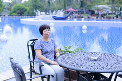 Chiński w średnim wieku kobiety obsiadanie na krześle obok basenu Zdjęcie Stock
