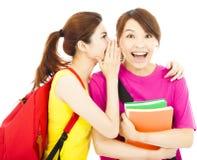 Chisme bonito del susurro de las chicas jóvenes a su compañero de clase Foto de archivo libre de regalías
