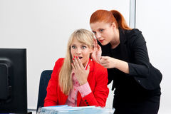 Chisme de dos colegues de la mujer en oficina Foto de archivo libre de regalías