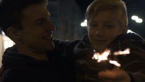 Chispa de observación feliz que quema, tradiciones de la familia, alegría del fuego artificial del padre y del hijo almacen de video