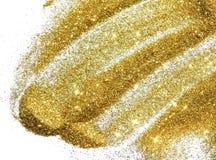 Chispa de oro del brillo en el fondo blanco imagenes de archivo