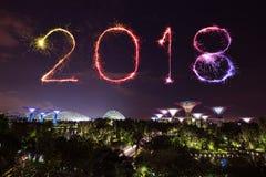 Chispa del fuego artificial de la Feliz Año Nuevo 2018 con los jardines por la bahía en Fotografía de archivo