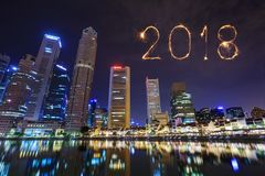 Chispa del fuego artificial de la Feliz Año Nuevo 2018 con la opinión del paisaje urbano Sing Fotos de archivo