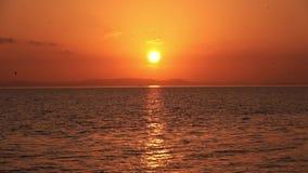 Chispas brillantes del sol rojo en la reflexión de la ondulación del agua metrajes