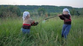 Chispas de los palillos ardientes Batalla de niños al dubankah ardiente los niños están luchando en un campo verde limpio carbone metrajes