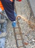 Chispea cuando el trabajador cortó un pedazo de hierro con un flexible Foto de archivo libre de regalías