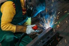 Chispea mientras que el soldador utiliza la antorcha a la soldadura Fotografía de archivo libre de regalías