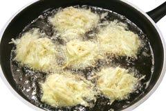 Chisporroteando las crepes de patata fritas en petróleo fotografía de archivo libre de regalías