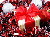 Chistmas background with gift box and red tinsel Royalty Free Stock Photos