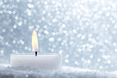 Chistmas candle glowing on glitter background. Stock Photo