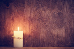 Chistmas candle glowing on wooden wall background. Stock Photo