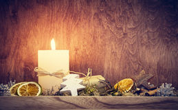Chistmas decoration with candle glowing on wooden wall background Royalty Free Stock Photo