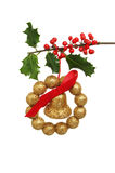Chistmas decoration and holly. Christmas decoration of gold bell bow and balls hanging from a fruiting holly bough Stock Photos