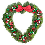 Chistmas Heart Shaped Wreath Decoration. Christmas heart shaped wreath decoration with red bow, baubles, holly, mistletoe and winter greenery on white background Stock Photos