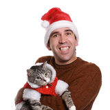 Chistmas Man and his Cat. A smiling young man wearing a santa hat and holding his cat, isolated against a white background Stock Image