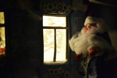 Chistmas photo with Father Frost and holiday`s windows. Plasticine Father Frost and shining windows - wanderful New Year card in Russian style Stock Photography