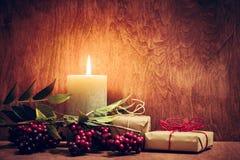 Chistmas présente, des cadeaux avec une bougie rougeoyant sur le fond en bois de mur photographie stock
