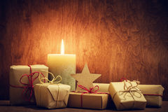 Chistmas presents, gifts with a candle glowing on wooden wall background. Royalty Free Stock Photo