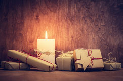 Chistmas presents, gifts with a candle glowing on wooden wall background. Royalty Free Stock Photography