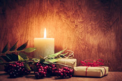 Chistmas presents, gifts with a candle glowing on wooden wall background. Stock Photography