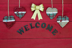 Chistmas welcome sign with red and green hearts and gold bow on wooden door Stock Image