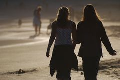Chit chat. Two girls catching up with a walk on the beach after work Royalty Free Stock Photo