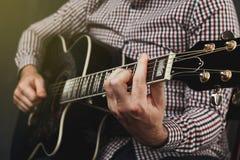 Chitarra acustica che sintonizza e che gioca vicino su Immagine Stock Libera da Diritti