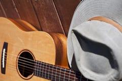 Chitarra acustica con il cappello fotografie stock