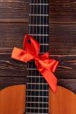 Chitarra acustica con l'arco rosso Fotografia Stock