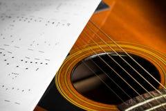 Chitarra acustica con la nota di canzone Fotografia Stock Libera da Diritti