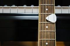 Chitarra acustica contro le chiavi del pianoforte a coda Fotografia Stock