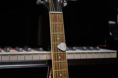 Chitarra acustica contro le chiavi del pianoforte a coda Immagini Stock Libere da Diritti