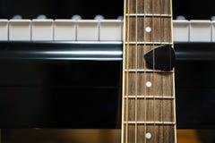 Chitarra acustica contro le chiavi del pianoforte a coda Immagine Stock