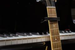 Chitarra acustica contro le chiavi del pianoforte a coda Immagini Stock