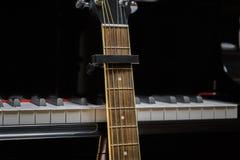 Chitarra acustica contro le chiavi del pianoforte a coda Fotografie Stock