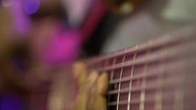 Chitarra acustica della sei-stringa L'uomo di colore gioca la chitarra Illuminazione del club Piano molto grande Macro fucilazion archivi video
