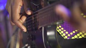 Chitarra acustica della sei-stringa L'uomo di colore gioca la chitarra Illuminazione del club Piano molto grande Macro fucilazion video d archivio