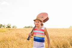 Chitarra acustica della tenuta del musicista e camminare nei campi di estate fotografie stock libere da diritti