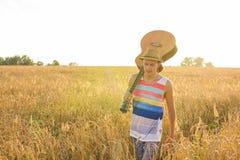 Chitarra acustica della tenuta del musicista e camminare nei campi di estate al tramonto fotografia stock