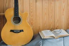 Chitarra acustica e libro aperto arancio con gli occhiali Fotografia Stock Libera da Diritti