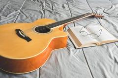 Chitarra acustica e libro aperto arancio con gli occhiali Fotografie Stock