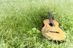 Chitarra acustica nel campo di erba Fotografia Stock