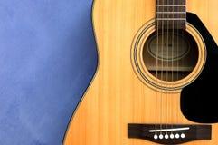 Chitarra acustica nella priorità bassa blu Fotografia Stock