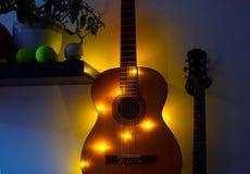 Chitarra acustica nella stanza che appende sulla parete su uno scaffale con una ghirlanda, interno della stanza, hobby domestico fotografie stock libere da diritti