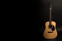 Chitarra acustica su un fondo nero sul lato destro della struttura Strumento a corda Struttura orizzontale Immagini Stock