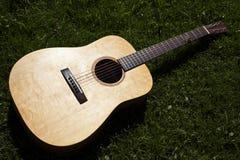 Chitarra acustica sulla chitarra acustica dell'erba su erba immagini stock libere da diritti