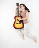 Chitarra addormentata e hudding della giovane donna Fotografia Stock