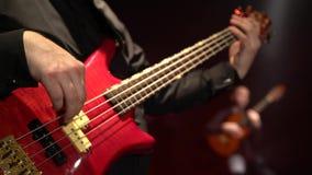 Chitarra bassa Due chitarristi giocano la chitarra Fine in su fiore della sfuocatura della priorità bassa all'interno come gli sg video d archivio